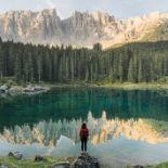 One person, looking very small gazing at the reflection of mountains in a lake.