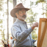 An older man in a cowboy hat, painting at an easel outside.