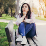 A young dark-haired woman sitting on a park bench, just gazing and thinking.