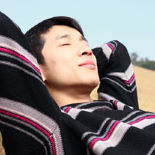 Young Asian man leaning back into his arms in the sun with his eyes closed.