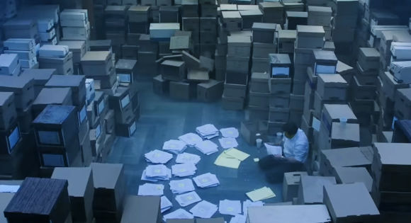 Mark Ruffalo as Robert Billott looking at piles of paper with information.