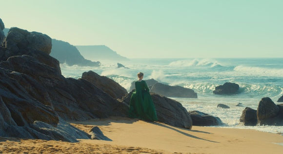 Adèle Haenel as Héloïse by the rocky shore of the beach in Portrait of a Woman on Fire