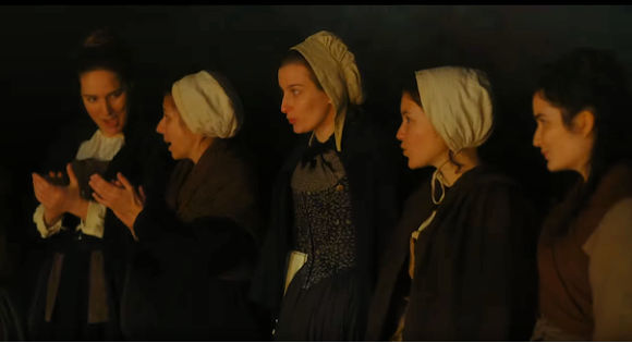 Five women in white caps singing in Portrait of a Woman on Fire