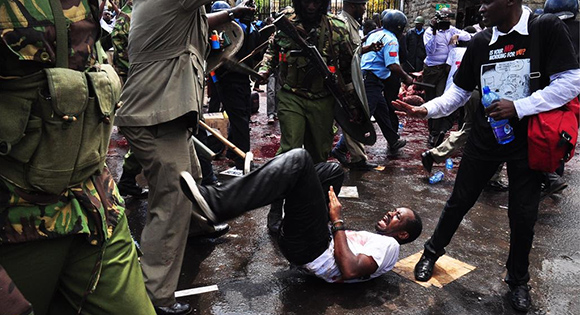 Boniface Mwangi being assaulted by the police during a demonstration.