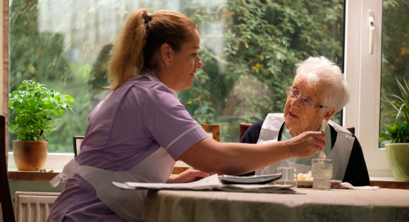 Debbie Honeywood as Abbie with a nursing home resident in Sorry We MIssed You