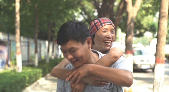 Liu Ximei hugging another AIDs patient who is smiling in Ximei