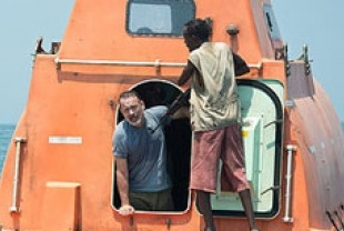 Tom Hanks as Captain Phillips and Barkhad Abdi as Muse