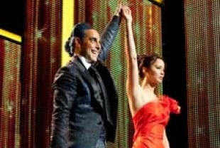 Stanley Tucci as Caesar and Jennifer Lawrence as Katniss